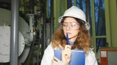 registros : Girl engineer in a white helmet carefully examines the gas equipment and thinks.