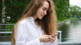 manikúra : Portrait of a beautiful young successful woman with a phone. European girl with long hair uses a smartphone and prints a message, slow motion