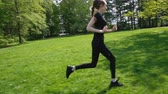 uzun saçlı : Young girl with a long braid has been running in the park. Young woman jogging in the summer, slow motion