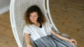 linho : Young European girl in a linen dress swings in a hammock-swing in a loft apartment. Beautiful woman resting in a hammock chair Vídeos