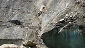 landslide : Slow motion rockfall in the mountains close up. Lumps of stones fall down from the melting glacier