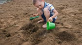 pours out : Little boy pours water from a bucket into a hole in the sand. Kids playing on the beach