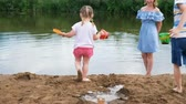 pours out : Little children play in the river in the summer. Mom looks after the kids. Stock Footage