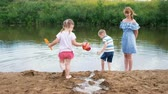 pours out : Little children play in the river in the summer, a girl and a boy are building a stream. Mom looks after babies during a walk Stock Footage