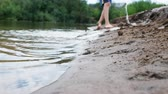 cubeta de agua : Blurred childish legs. Children playing on the river with sand