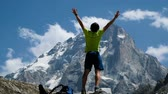 góral : Man raises hand up in the mountains in a hike standing on a stone, a beautiful view opens up. Concept of victory and success, the achievement of the goal, slow motion Wideo