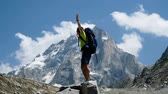 góral : Man tourist with a backpack raises his hands up in the mountains in the campaign after climbing and spinning around. Concept of victory and success, goal achievement, slow motion Wideo