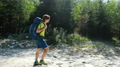 пеший туризм : Young man tourist in trekking boots with a backpack walking in a hike against a beautiful mountain landscape, camera movement Стоковые видеозаписи
