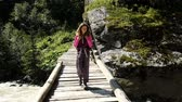 кресты : Woman tourist with a backpack walks along a wooden bridge across a fast mountain stream, slow motion Стоковые видеозаписи