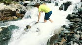 gázló : Man crosses the bare mountain stream to the ford barefoot Stock mozgókép