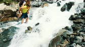 demolida : Man carries a woman with a backpack over a mountain stream on her back barefoot into a ford. The guy helps the girl to get over the cold and fast stream