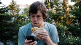 prejudicial : Man using smartphone and eats khachapuri - bread with meat or beans on the street, slow motion