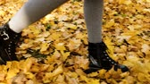 throws up : Woman walking on fallen leaves in golden autumn, slow motion