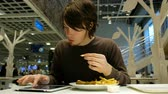 vício : Man uses a tablet in a restaurant and eats fast food in a restaurant