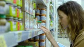 produtos químicos : Young woman with a tablet carefully examines the composition of baby food in a supermarket