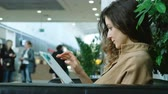 computador tablet : Businesswoman uses a tablet in a shopping mall chair, a modern girl works on a laptop computer Stock Footage