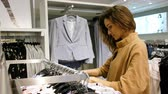 suitable : Young woman chooses a blouse in a clothing store