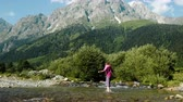 кресты : Woman tourist crosses the creek on the background of a mountain landscape Стоковые видеозаписи