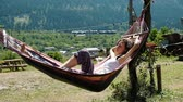 trapo : Girl sleeping in a hammock on the nature against the background of green mountains, slow motion