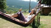 hamak : Woman is resting and swinging in a hammock and using the phone in nature Dostupné videozáznamy