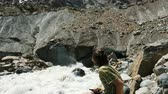 landslide : Man looks at the falling stones from the glacier. Rockfall in a tourist spot Stock Footage