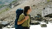 góral : Tourist stands with a backpack near a fast river and looks at the mountains