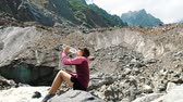 körülmények : Girl tourist drinks water from a bottle in the mountains, slow motion Stock mozgókép