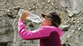 isteyen : Woman tourist drinks water from a plastic bottle in the mountains close-up