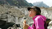 クエンチ : Woman tourist eats bread in the mountains close up 動画素材