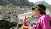 クエンチ : Woman tourist drinks water and eats bread in the mountains close up