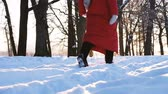 Girl in a red down jacket and black felt boots walks through the snow at sunset in the park, slow motion