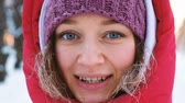 Portrait of a beautiful caucasian girl with blue eyes cold winter in a close-up park, slow motion