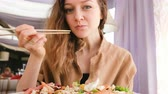 Young beautiful girl eating salad with fish sticks in a Japanese restaurant