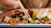 Girl eating a salad with raw fish sticks in a restaurant closeup