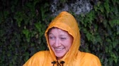 esős : Portrait of smiling woman in a yellow raincoat in the pouring rain, slow motion