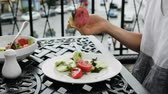 Slim woman eating vegetable salad with a fork in an outdoor restaurant