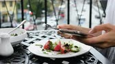 Woman uses the phone and eats a vegetable salad in a restaurant on the street Stock Footage