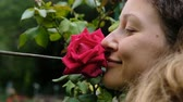 rose garden : Woman smelling a big red rose on a tree with closed eyes close up