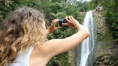 захват : Curly woman induces a focus on the phone screen and photographs a waterfall in the park