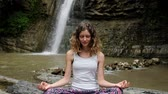 consciência : Happy girl meditates in the lotus position and opens her eyes while awakening from the practice, slow motion