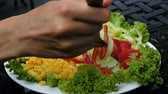 dietetica : Woman takes a fork with fresh pepper, cucumber and tomato with vegetable plate close-up Archivo de Video