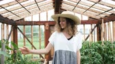 cheirando : Girl farmer in a straw hat and dress goes to the greenhouse and enjoys the harvest