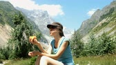 prazer : Woman sits on a stone and eats a peach on a background of mountains
