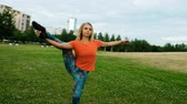 formacion : Gymnast lifts a leg in a vertical twine in a city park, camera movement Archivo de Video