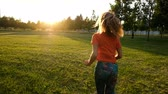 ćwiczenia : Sports woman doing jogging on the grass on sunset in a city park, slow motion