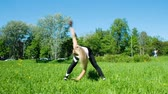 city lifestyle : Flexible girl doing warm up in nature - waving her arms from side to side in the slope, slow motion Stock Footage