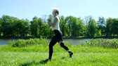 formacion : Sporty girl holds warm-up in nature - jumps and pumps legs muscles, slow motion