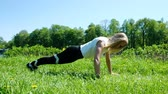 prensado : Athletic woman wrung out in the grass on the nature, girl exercises in the park slow motion