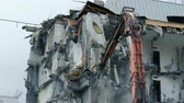 housenka : Excavator destroys the old building. Demolition work, pieces of concrete and reinforcement fall down