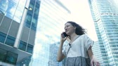 Business girl in a dress talking on the phone on the background of skyscrapers Stok Video